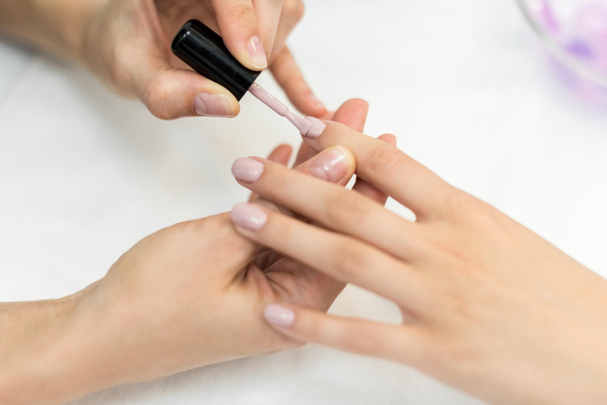 Frau lackiert anderer Frau die Nägel