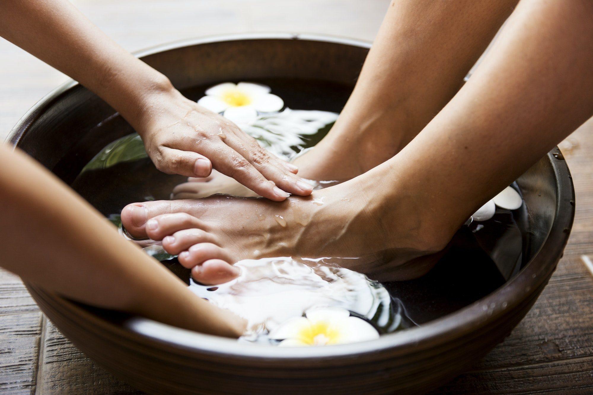 Füße werden massiert in einer Schüssel vor Wasser