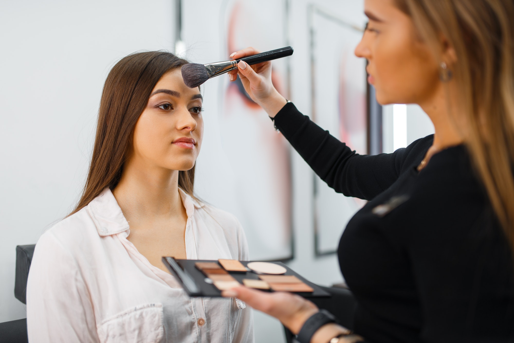 Cosmetician with brush and woman, cosmetics store